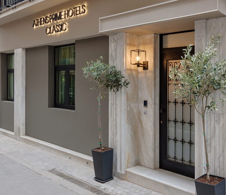The Classic by Athens Prime Hotels entrance with marble doorway, and glowing sign.