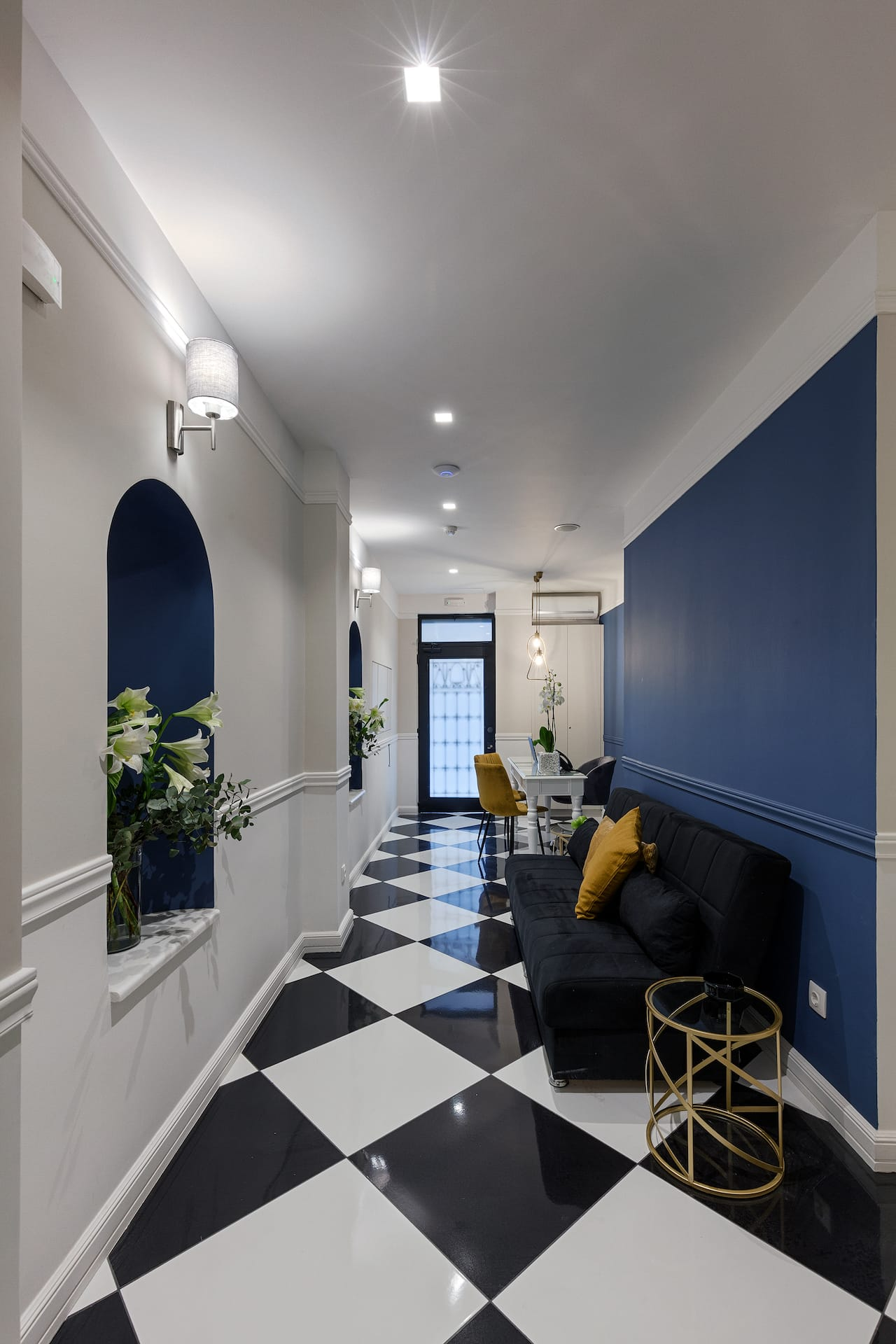 The reception area lounge of the Classic by Athens Prime Hotels. Dark blue sofa with yellow pillows.