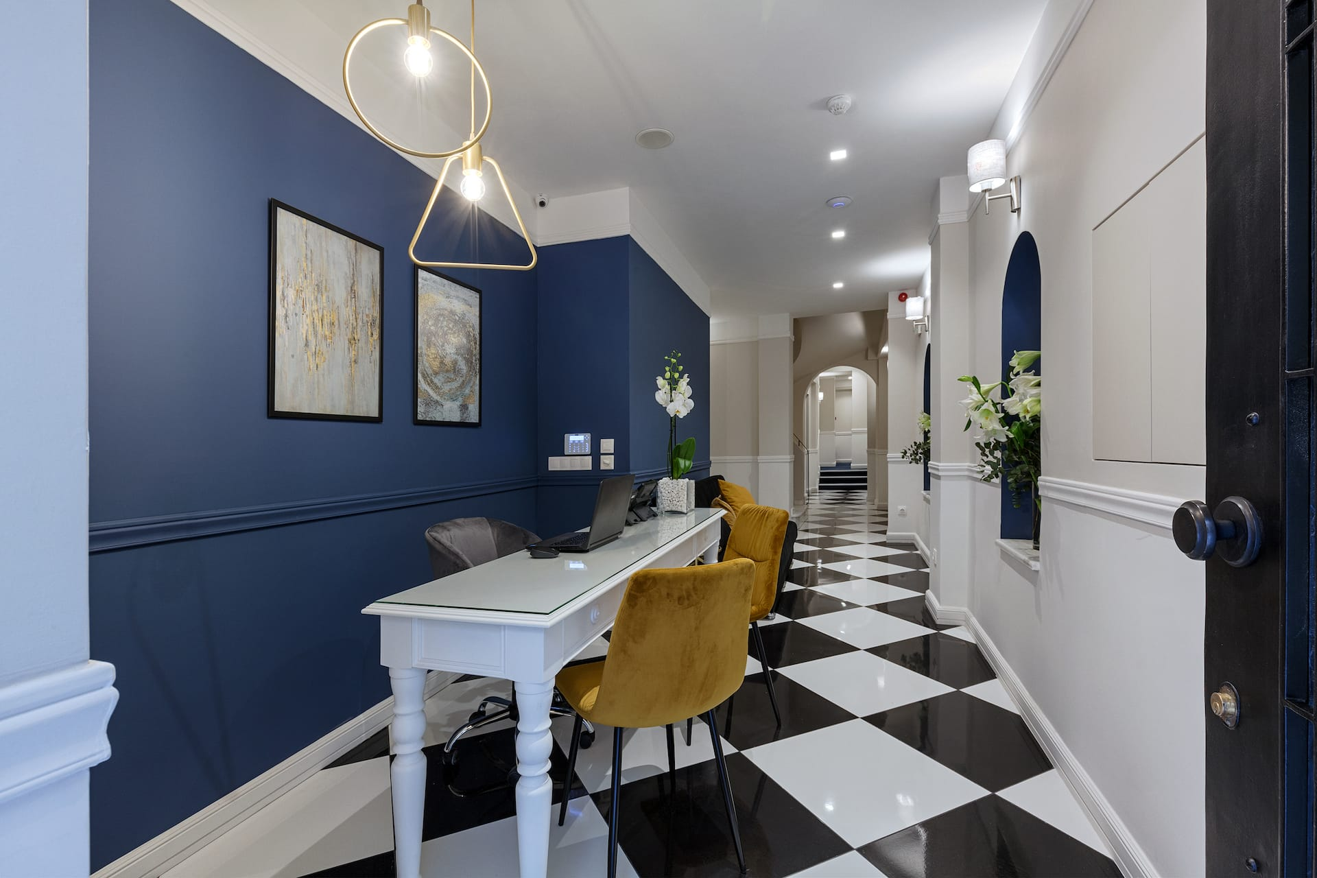 The reception area of the Classic by Athens Prime Hotels. Black and white floors with blue walls.