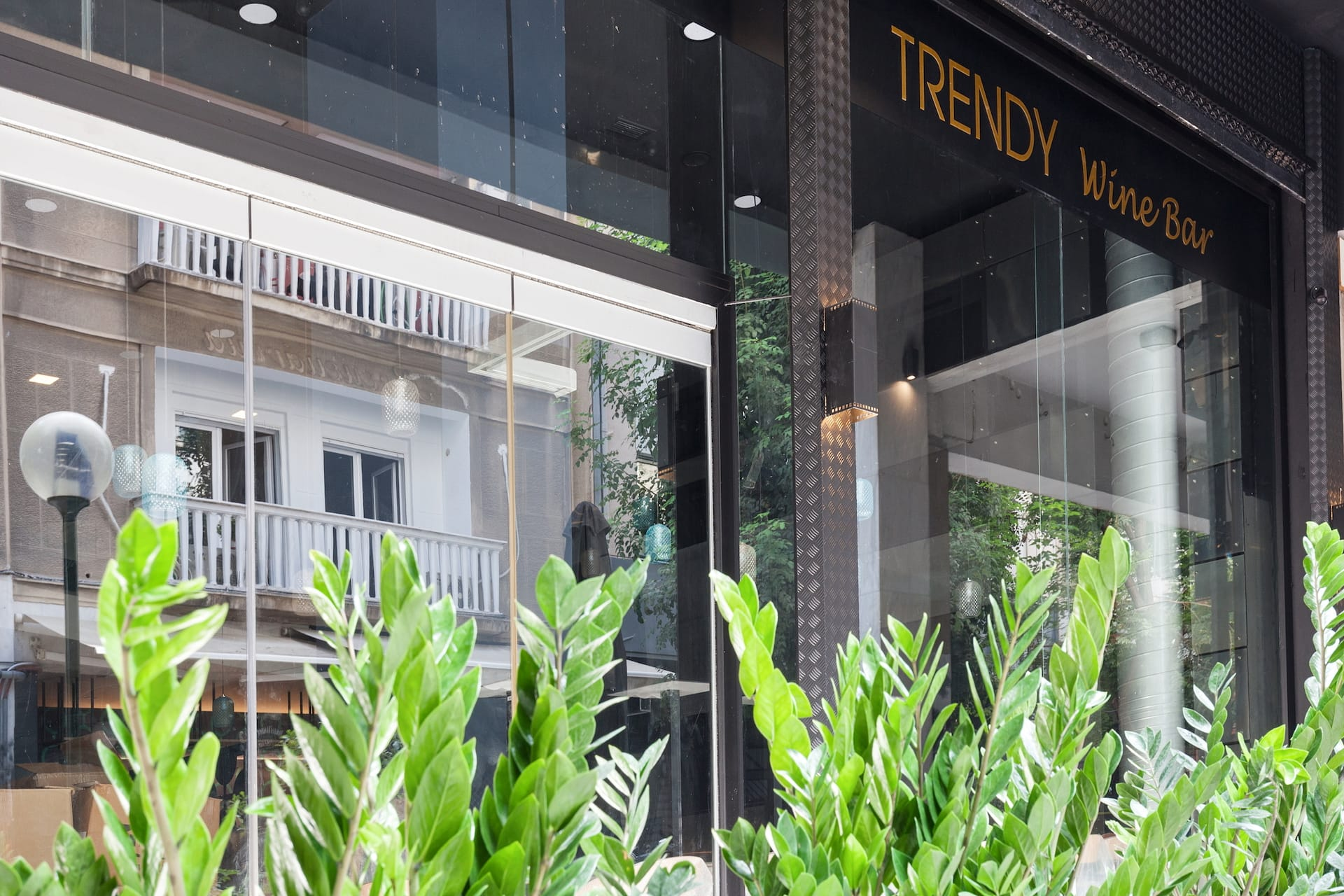 The Trendy by Athens Prime Hotels entrance with big black doorway, and gold sign.