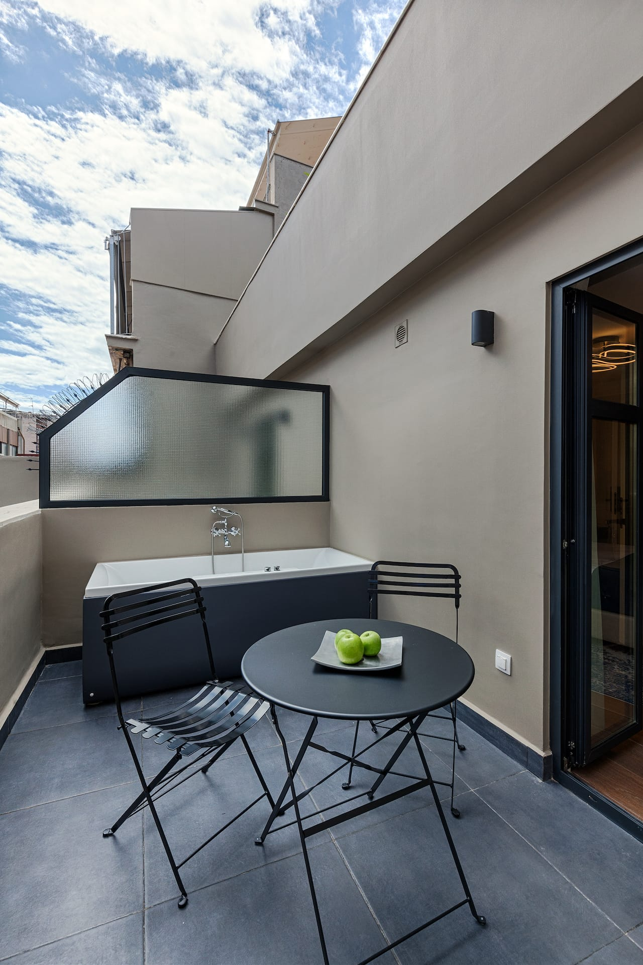 Outdoor hot tub, black tables and chairs located on the veranda of the Deluxe Room Hot Tub.