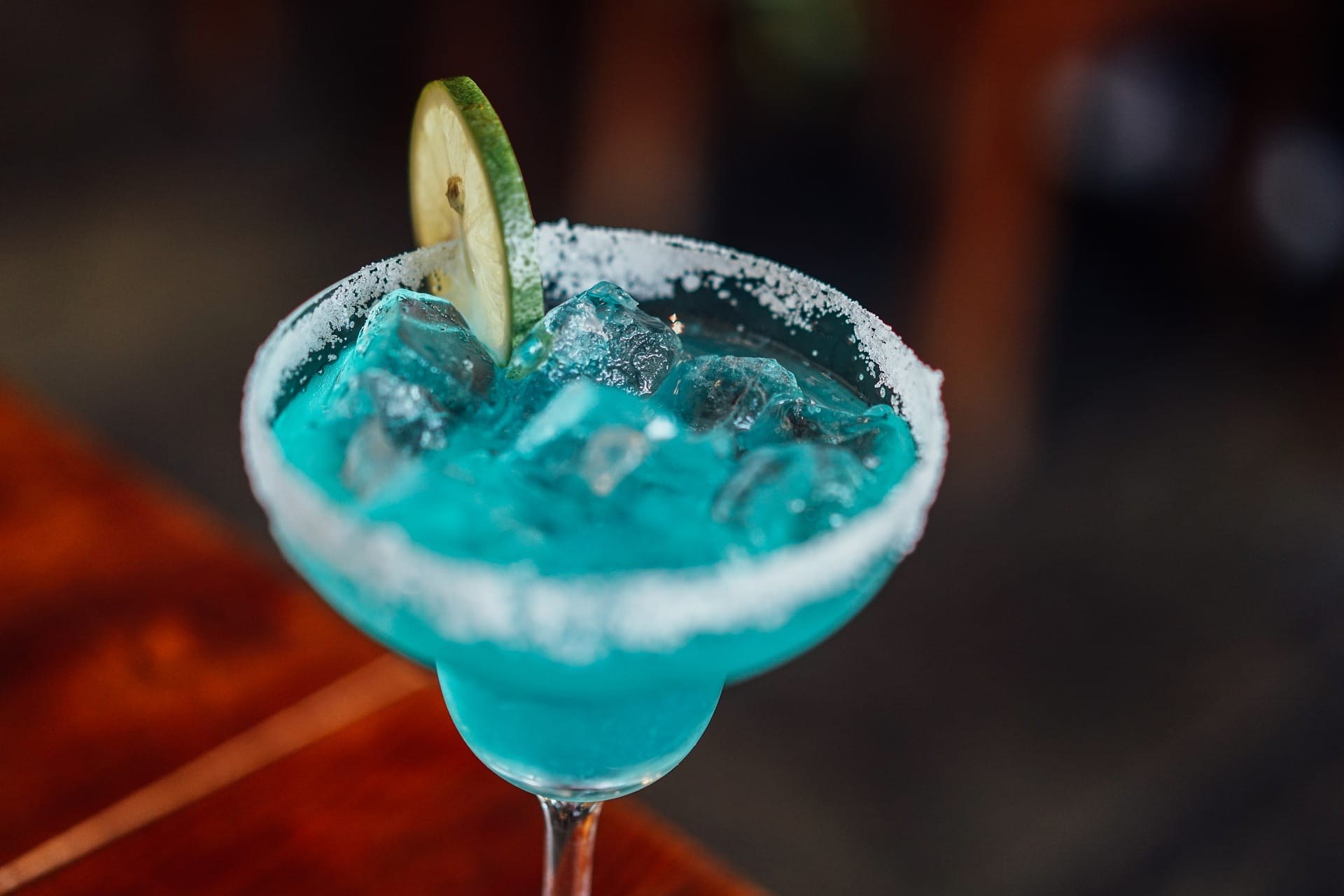 Beautiful blue cocktail filled with ice and with a slice of lime and salt around the glass rimm.